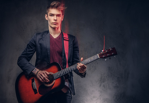 istock Stylish young musician with stylish hair in elegant clothes, playing on an acoustic guitar. 1048391442