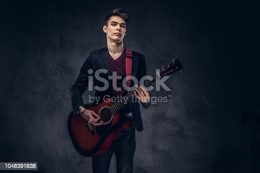 istock Stylish young musician with stylish hair in elegant clothes, playing on an acoustic guitar. 1048391638