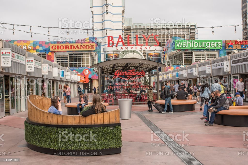 Stylish young people dining at an outdoor booth in front of Bally's Las Vegas stock photo