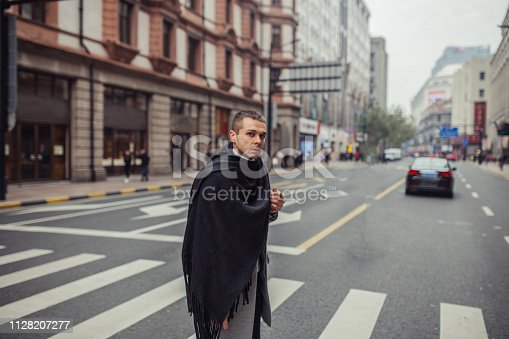 Fashionable handsome man wearing gray coat, long, black scarf and black backpack, crossing the street.