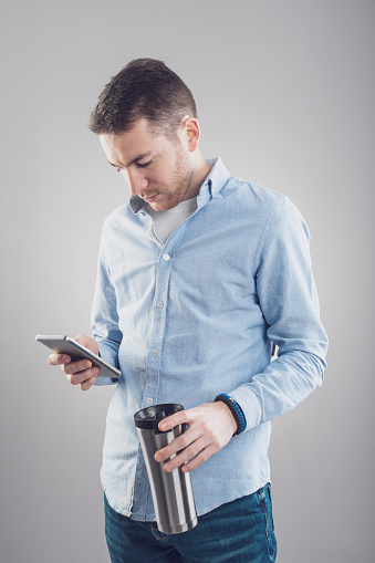 825083556 istock photo Stylish young trendy man typing message on cell phone. Man texting on phone 1086564232