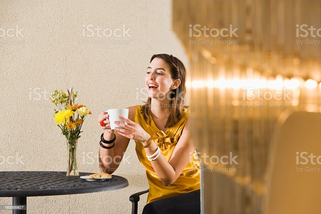Stylish young woman drinking coffee at cafe table royalty-free stock photo