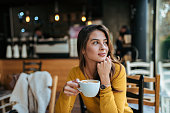 Stylish young woman drinking coffee at the cafe, looking away.