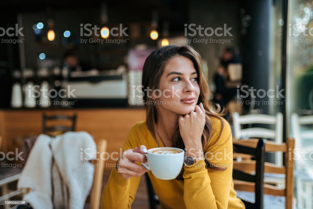 Stylish young woman drinking coffee at the cafe, looking away. stock photo