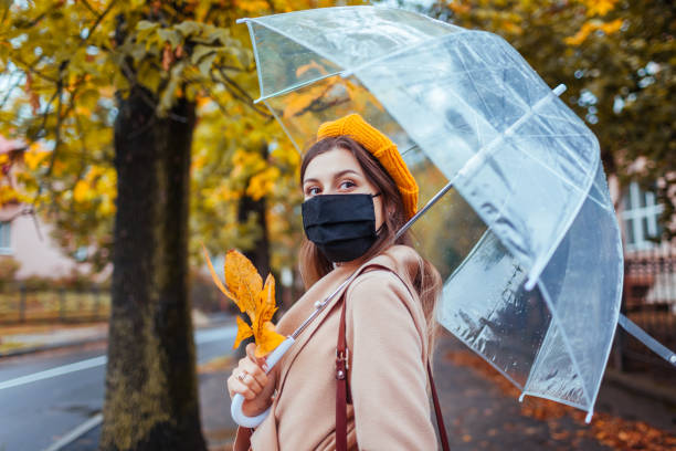 Stylish young woman in protective mask walking along autumn city street under transparent umbrella during rain.