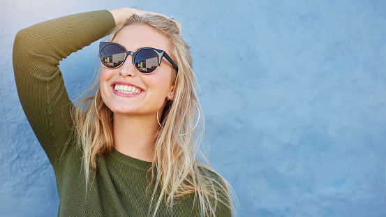 istock Stylish young woman in sunglasses smiling 541271164
