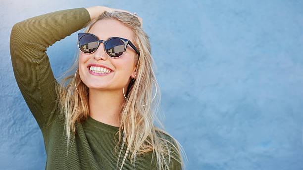 stylish young woman in sunglasses smiling - insouciance photos et images de collection