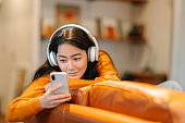 istock Stylish young woman listening to music at home 1207317848