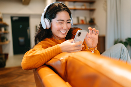 A stylish young woman is sitting on a sofa and listening to music with a wireless bluetooth headphones connected to her smart phone in the living room at home.