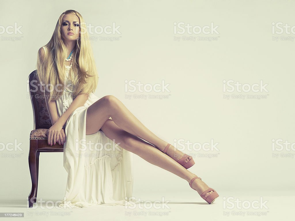 Stylish young woman posing on chair stock photo