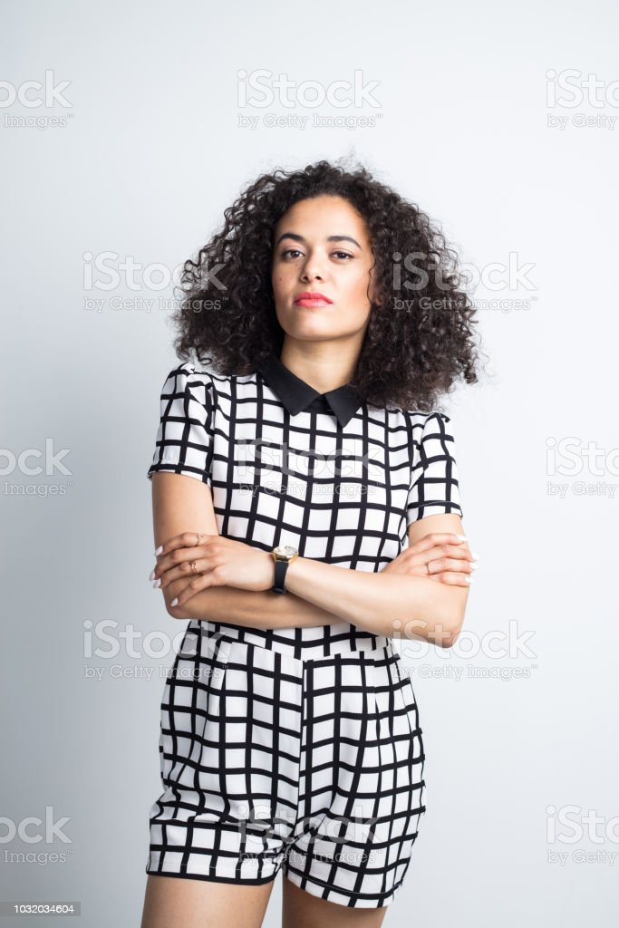 Stylish young woman posing on gray background Portrait of attractive young woman in stylish outfit standing with her arms crossed and looking at camera against gray background 20-24 Years Stock Photo