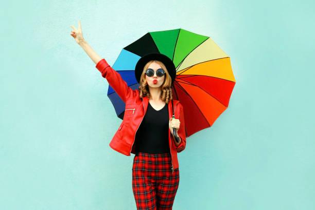 Stilvolle junge Frau mit bunten Regenschirm bläst rote Lippen senden süße Luft Kuss, tragen rote Jacke, schwarze Mütze auf blauem Wandhintergrund – Foto