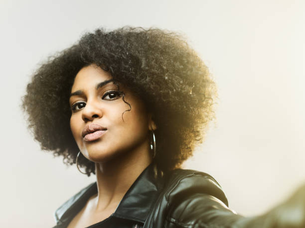 Stylish young woman with curly hair looking at camera stock photo