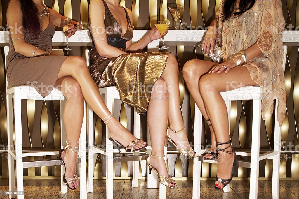 Stylishly Dressed Women Sitting At The Bar stock photo