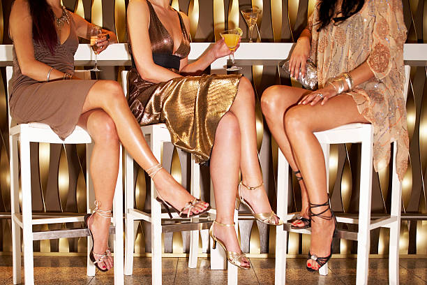 Stylishly Dressed Women Sitting At The Bar Low section of three stylishly dressed women sitting legs crossed at the bar evening wear stock pictures, royalty-free photos & images