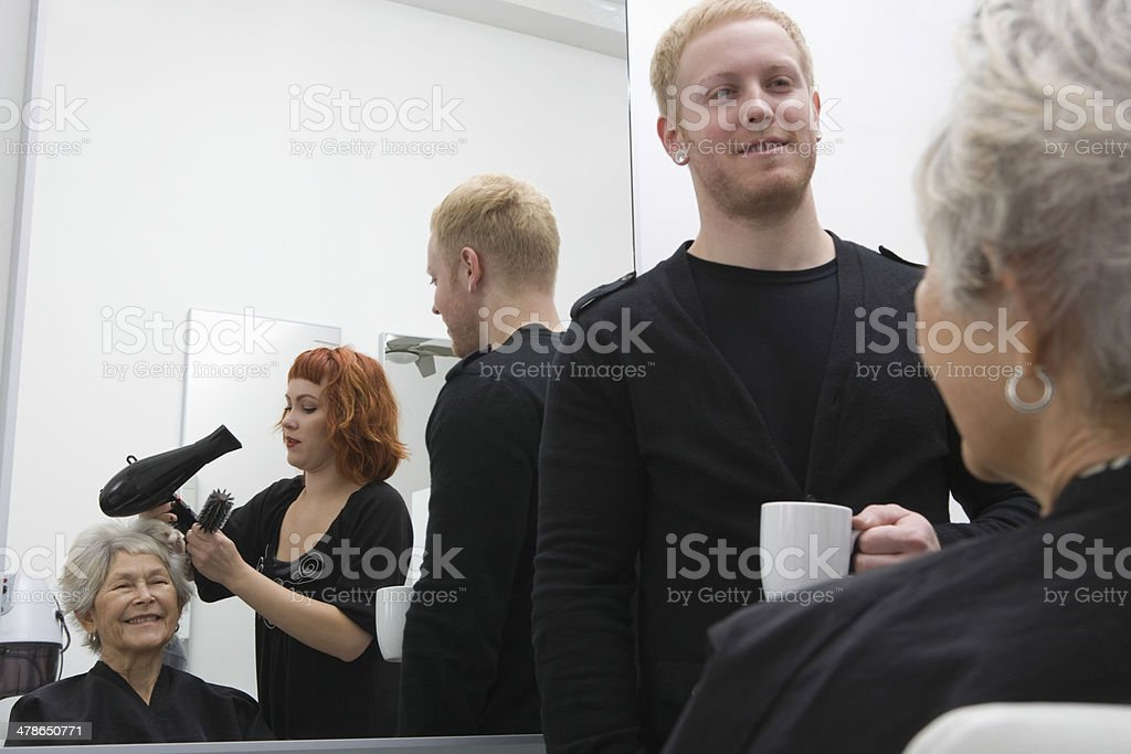 Stylist Blow Drying Senior Woman's Hair In Salon stock photo