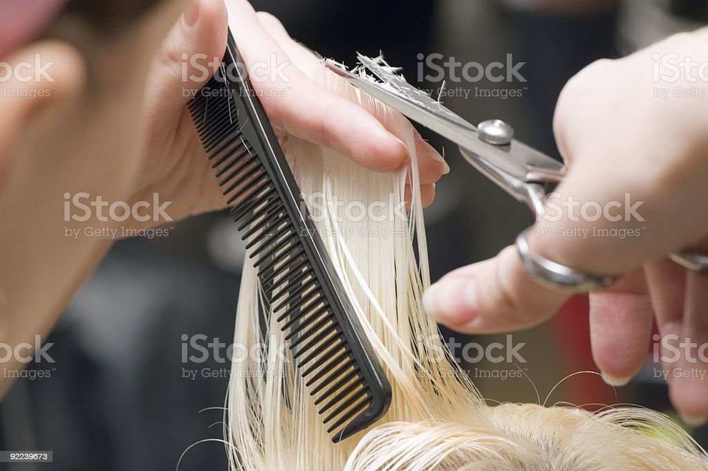 Stylist cutting a child's blonde hair with scissors stock photo