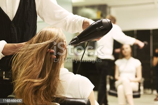 Hairdresser Drying Woman's Hair With Hair Dryer In Beauty Studio. Selective Focus, Empty Space