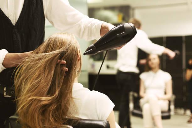 stylist drying girl's hair with hair dryer in beauty salon - hairdresser стоковые фото и изображения