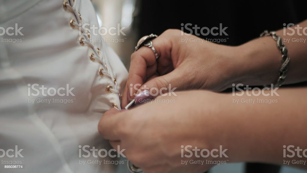 Stylist helps to tighten the corset of a historical dress on woman. 18th century look. Hands close-up stock photo