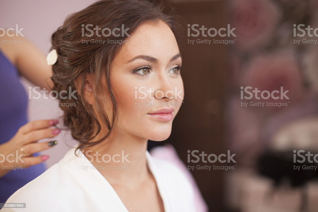 Stylist pinning up a bride's hairstyle stock photo
