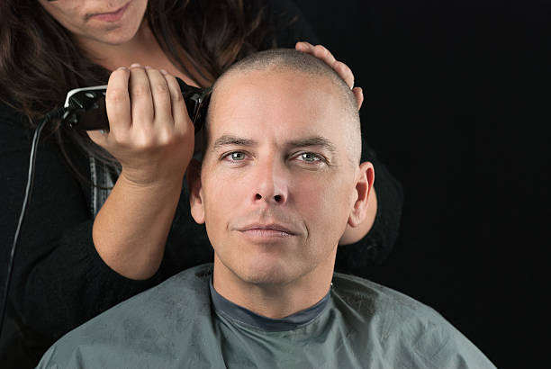 Stylist Shaves Mans Head Close-up of a hair stylist using clippers to shave her Clients head. shaved head stock pictures, royalty-free photos & images