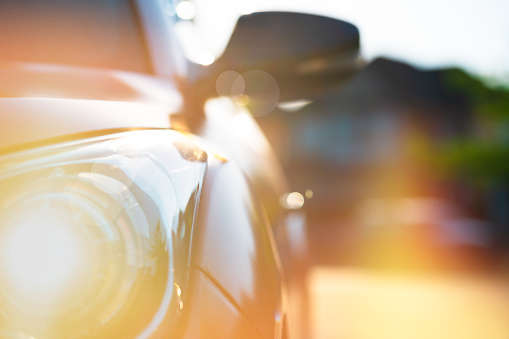Highly Stylizes depiction of a generic vehicle in golden light of summertime - close up of front headlight and side mirror.