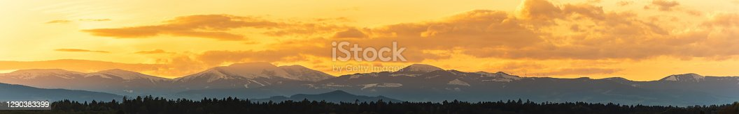 istock Styrian Lavanttaler Alps covered with snow in orange light of sunset. Background or banner 1290383399