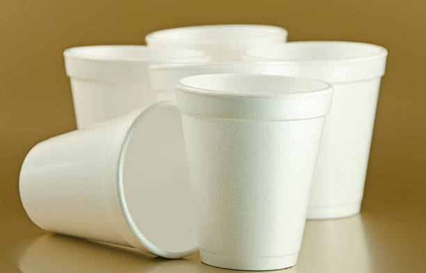 Styrofoam Cups Styrofoam cups on a gold background.. polystyrene stock pictures, royalty-free photos & images