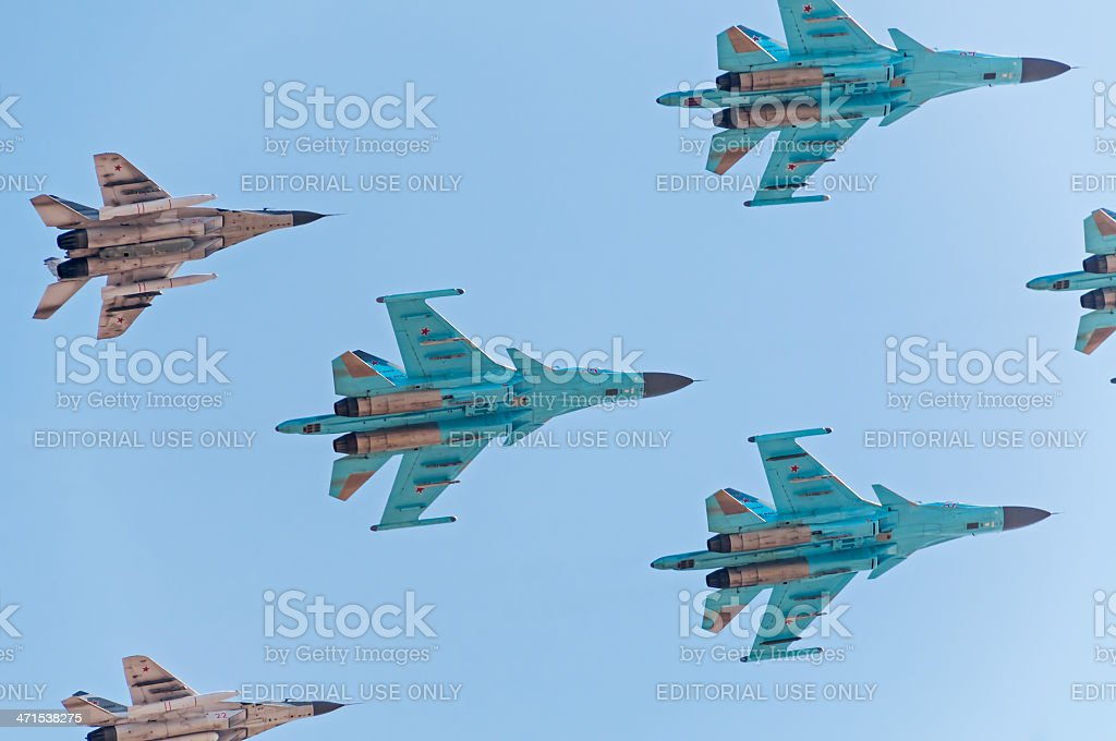 Su-34 and MiG-29 fly closely against blue sky background royalty-free stock photo