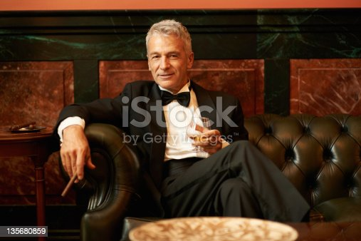 Portrait of a sophisticated senior man sitting on couch holding cigar and glass of brandy