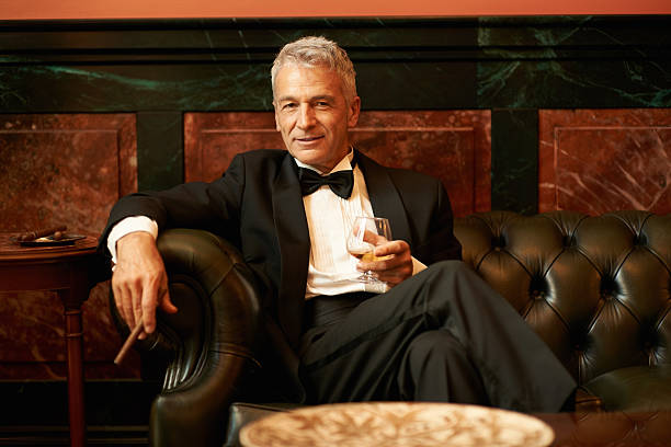 Suave man in a cigar lounge Portrait of a sophisticated senior man sitting on couch holding cigar and glass of brandy high society stock pictures, royalty-free photos & images