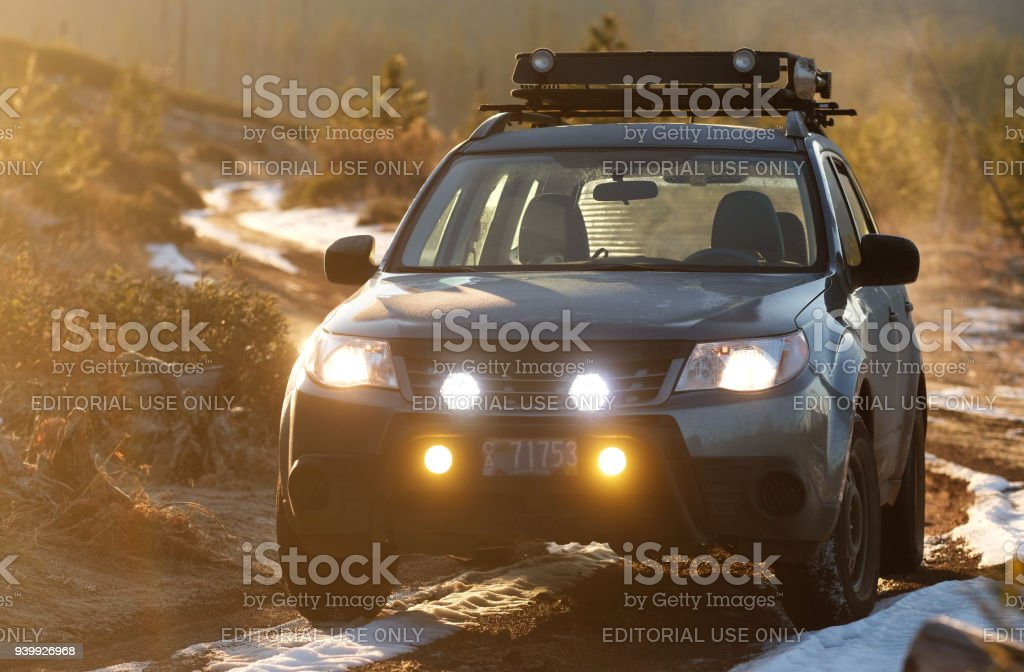 Subaru Forester on Wilderness Dirt Road with Rising Sun