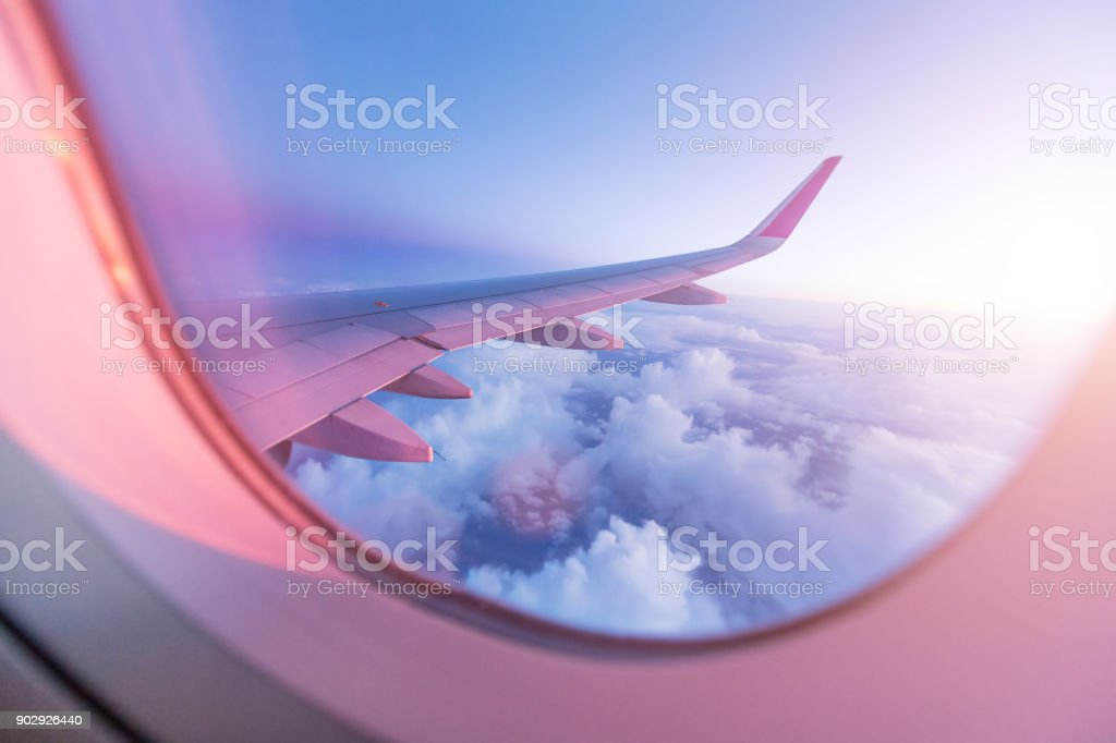 SuBeautiful sunset with cloudy sky from the airplane window stock photo