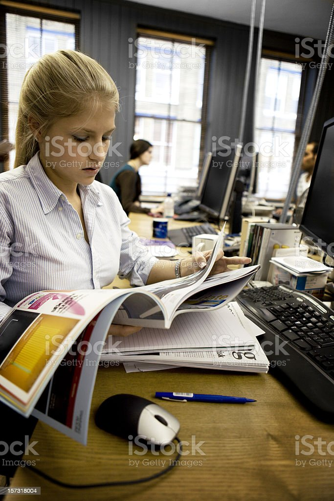 Sub-editor of a publishing team browsing through a magazine royalty-free stock photo