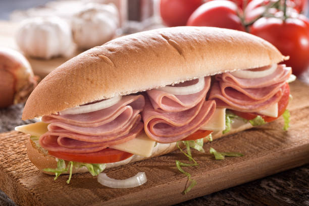 Submarine Hoagie Sandwich A delicious submarine sandwich with deli meats, lettuce, tomato, onion and cheese on a sub bun. submarine sandwich stock pictures, royalty-free photos & images