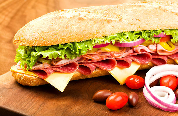 Submarine Sandwich Footlong Salami, Ham, cheese sub with lettuce, tomato, onion and peppers submarine sandwich stock pictures, royalty-free photos & images