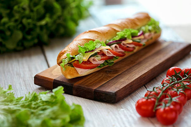 Submarine Sandwich  Submarine Sandwiches- Turkey, Ham and Cheese, Swiss with Lettuce , salad  and Tomato on Crusty Buns on wooden table submarine sandwich stock pictures, royalty-free photos & images