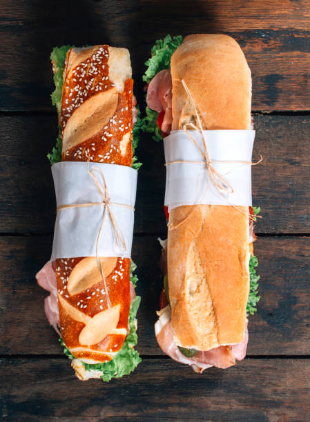 Submarine sandwiches Submarine sandwiches with vegetables and prosciutto on wooden background with blank space submarine sandwich stock pictures, royalty-free photos & images