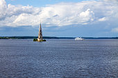 A submerged bell tower and a white cruise ship on the Volga river in Kalyazin Russia on a cloudy summer day and a copy space