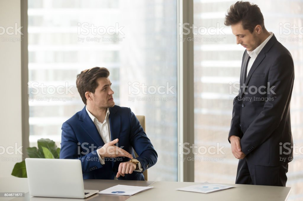 Subordinate receiving reprimand from boss for being late, missing deadline stock photo
