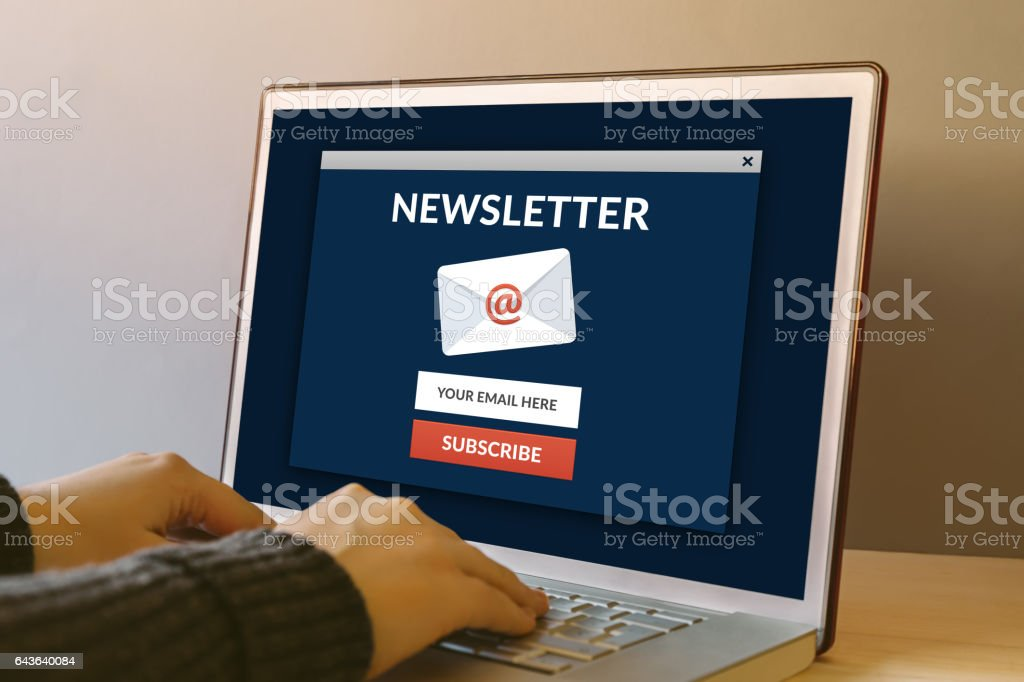 Subscribe newsletter concept on laptop computer screen on wooden table stock photo