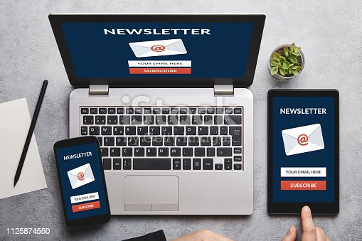 Subscribe newsletter concept on laptop, tablet and smartphone screen over gray table. All screen content is designed by me. Flat lay