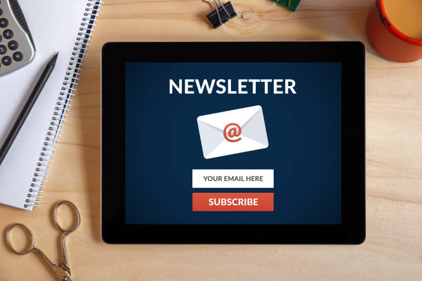 Subscribe newsletter concept on tablet screen with office objects stock photo