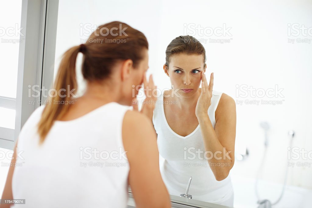 Subtle cosmetics adding to her beauty A pretty young woman applying lotion to the skin around her eyes in the mirror Women Stock Photo