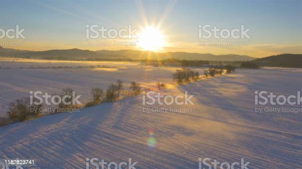 Photo of LENS FLARE: Subtle mist rising from the snowy fields on a sunny winter morning.
