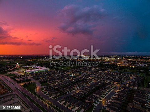 istock Suburb at night as a Red Glowing Sun sets behind horizon Lights turn on in the homes below Suburb of Austin , Texas , USA 915792856