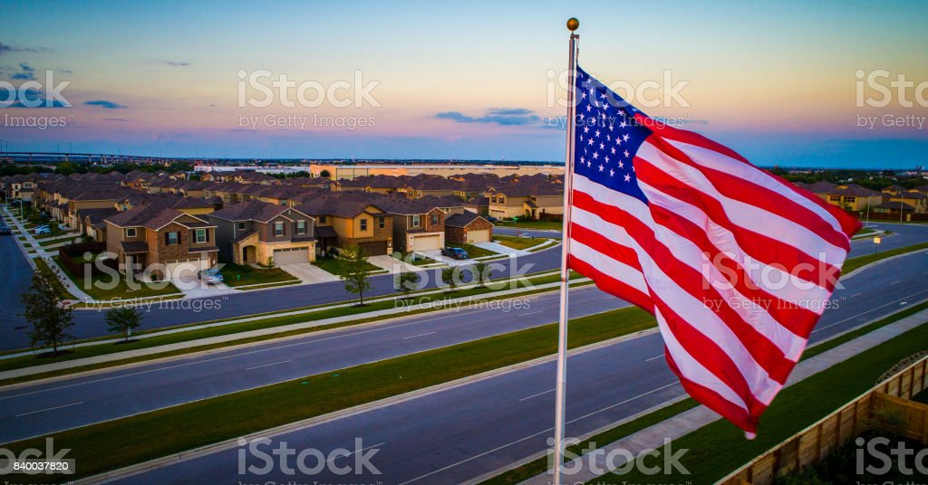 Suburb flying American Pride United States Flag Flying during amazing colorful Sunset stock photo
