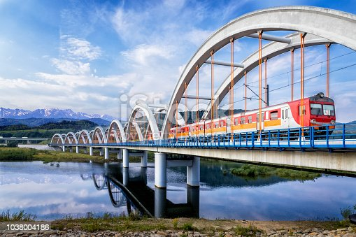Suburb passenger train drive through the viaduct towards the Tatra Mountains, Poland