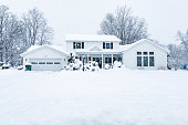 Front elevation view from the street in front of a colonial style home built in the 1970's. Photo shot during an extreme February winter blizzard snow storm in a suburban residential district neighborhood near the city of Rochester, in western New York State.